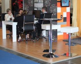 BNV Kiállítás, 2012 - Impala Bútorkereskedő Kft. fehér bárszékei és a háttérben forgószékei, illetve magasfényű fehér asztala